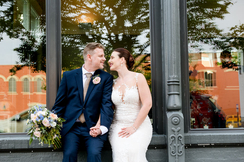 Bride and Groom smiling at each other outside of 5Eleven Palafox, Classic Pensacola Wedding, Lazzat Photography, Florida Wedding Photographer