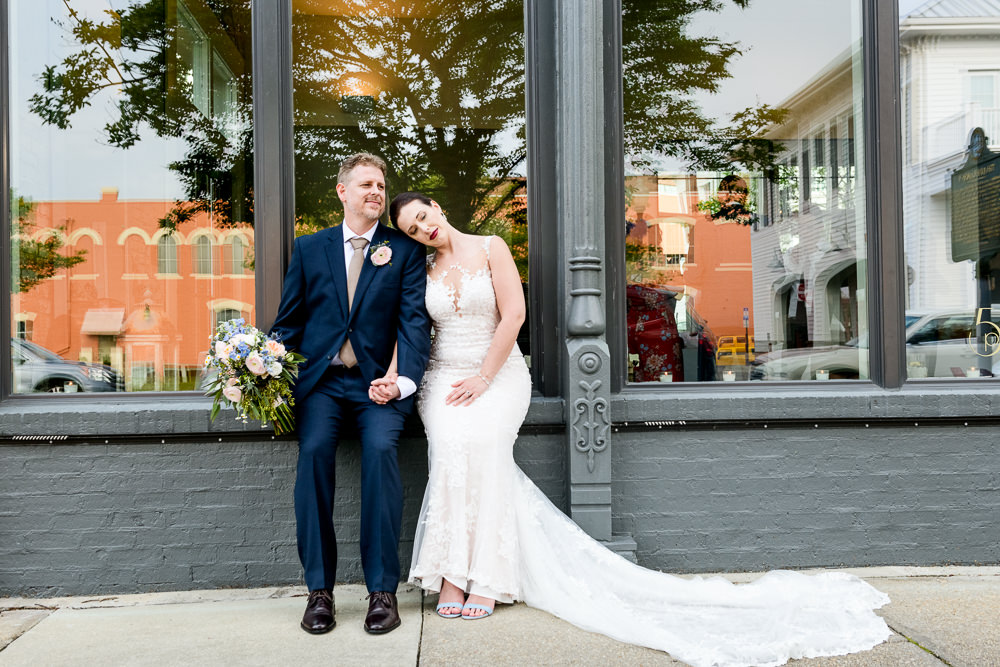 Groom looking into the distance while his Bride leans on him outside of 5Eleven Palafox, Classic Pensacola Wedding, Lazzat Photography, Florida Wedding Photographer