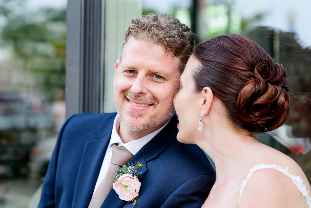 Groom smiling at the camera while his Bride leans on him outside of 5Eleven Palafox, Classic Pensacola Wedding, Lazzat Photography, Florida Wedding Photographer