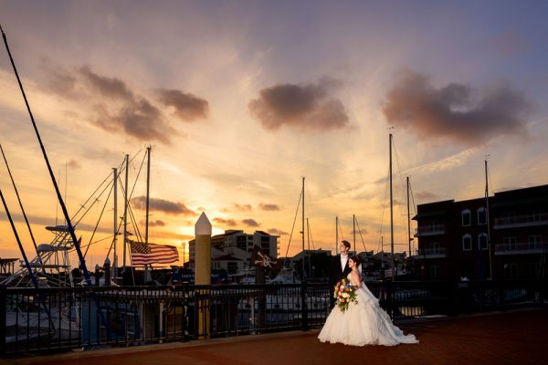 Bride and Groom at sunset with sailboats and an American flag, Romantic Catholic Wedding, Pensacola Florida Wedding Photographer, Lazzat Photography