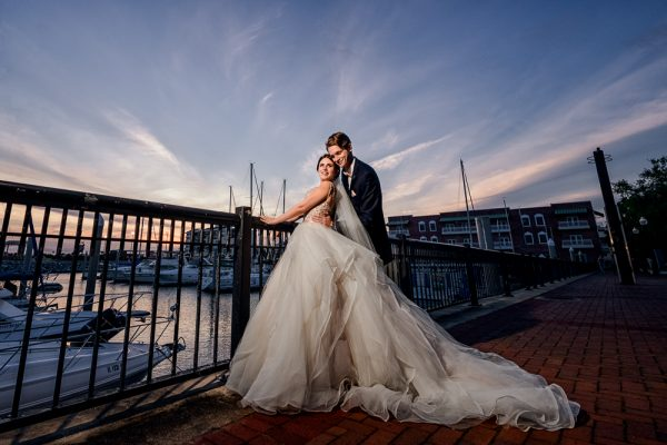 Bride and Groom looking at each other on the railing by the water at sunset, Romantic Catholic Wedding, Pensacola Florida Wedding Photographer, Lazzat Photography