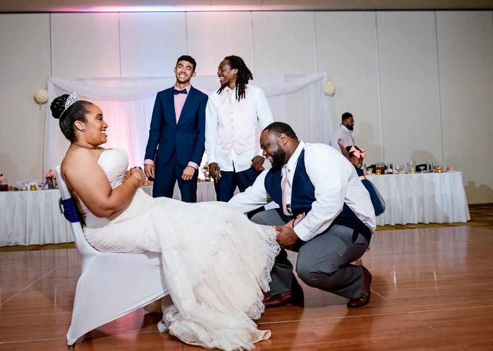 Groom taking off the Bride's garter, Blue and Pink Wedding, The Soundside Club, Elegant Ballroom Wedding, Lazzat Photography, Florida Wedding Photography