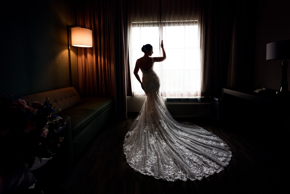 Bride looking out the window, lace wedding dress, Holiday Inn Express Pensacola Downtown, Classic Pensacola Wedding, Lazzat Photography, Florida Wedding Photographer