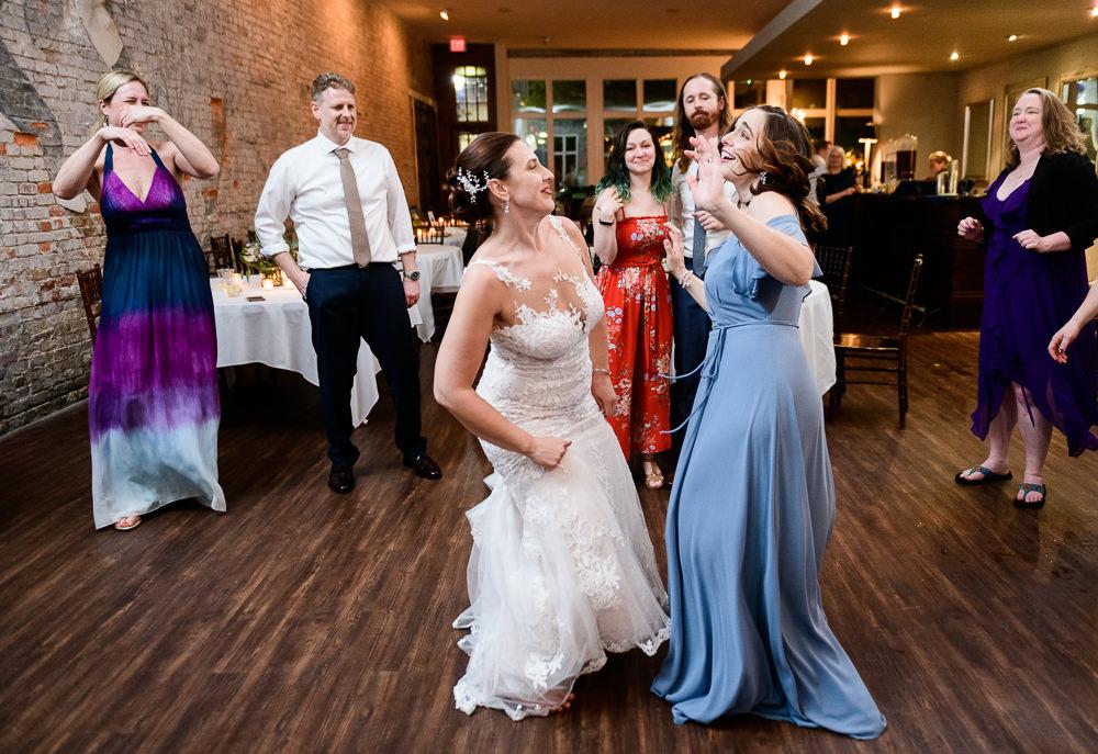 Bride and Bridesmaid dancing, 5Eleven Palafox, Classic Pensacola Wedding, Lazzat Photography, Florida Wedding Photographer