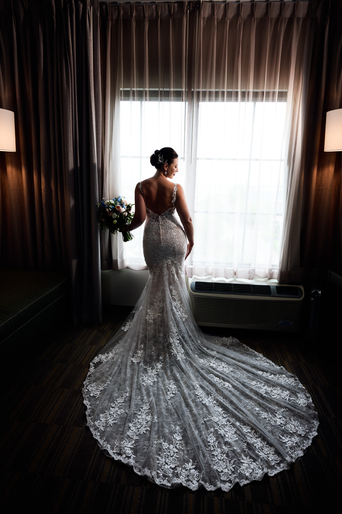 Bride posing by the window, lace wedding dress, Holiday Inn Express Pensacola Downtown, Classic Pensacola Wedding, Lazzat Photography, Florida Wedding Photographer