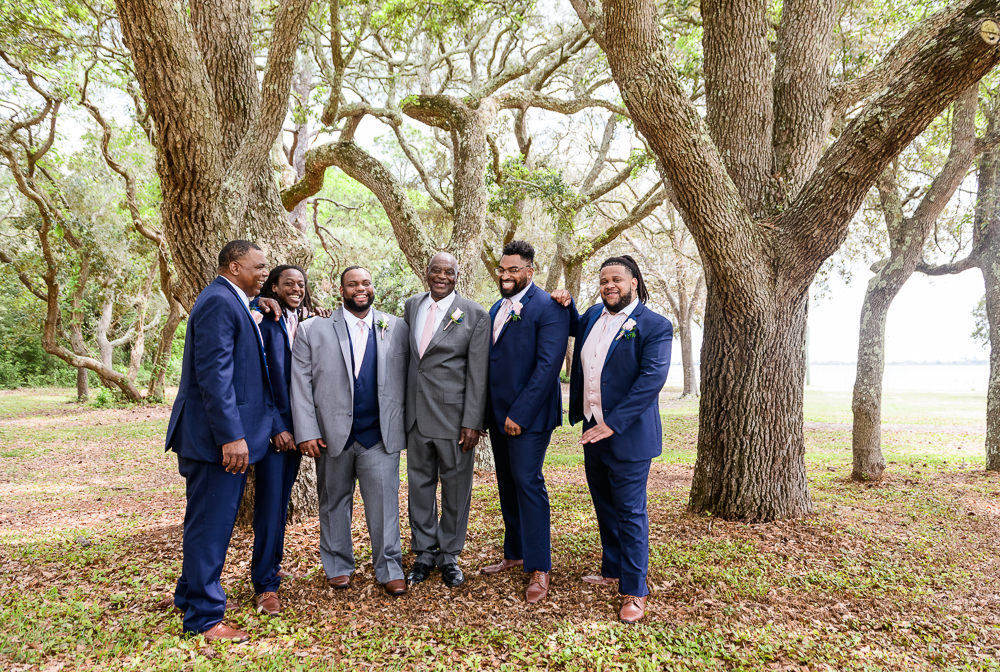 Groom and Groomsmen posing by the trees, Blue and Pink Wedding, The Soundside Club, Elegant Ballroom Wedding, Lazzat Photography, Florida Wedding Photography
