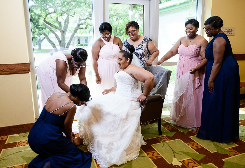 Bridesmaids putting on Bride's shoes, Blue and Pink Wedding, The Soundside Club, Elegant Ballroom Wedding, Lazzat Photography, Florida Wedding Photography