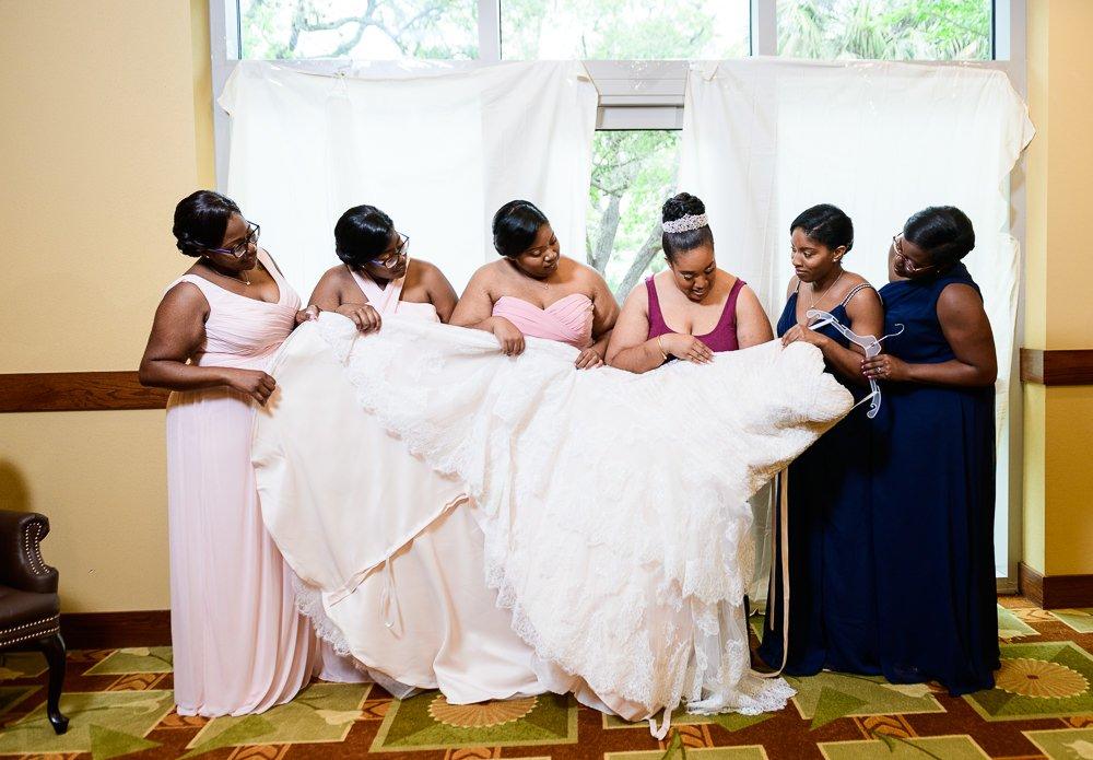 Bride and Bridesmaids looking at wedding dress, The Soundside Club, Elegant Ballroom Wedding, Lazzat Photography, Florida Wedding Photography