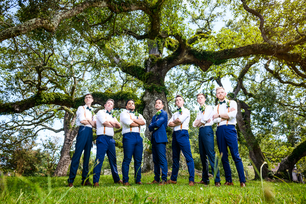 Groom and Groomsmen crossing their arms, blue and green wedding, The Garden Center, Pensacola Garden Wedding, Lazzat Photography, Florida wedding photographer photography