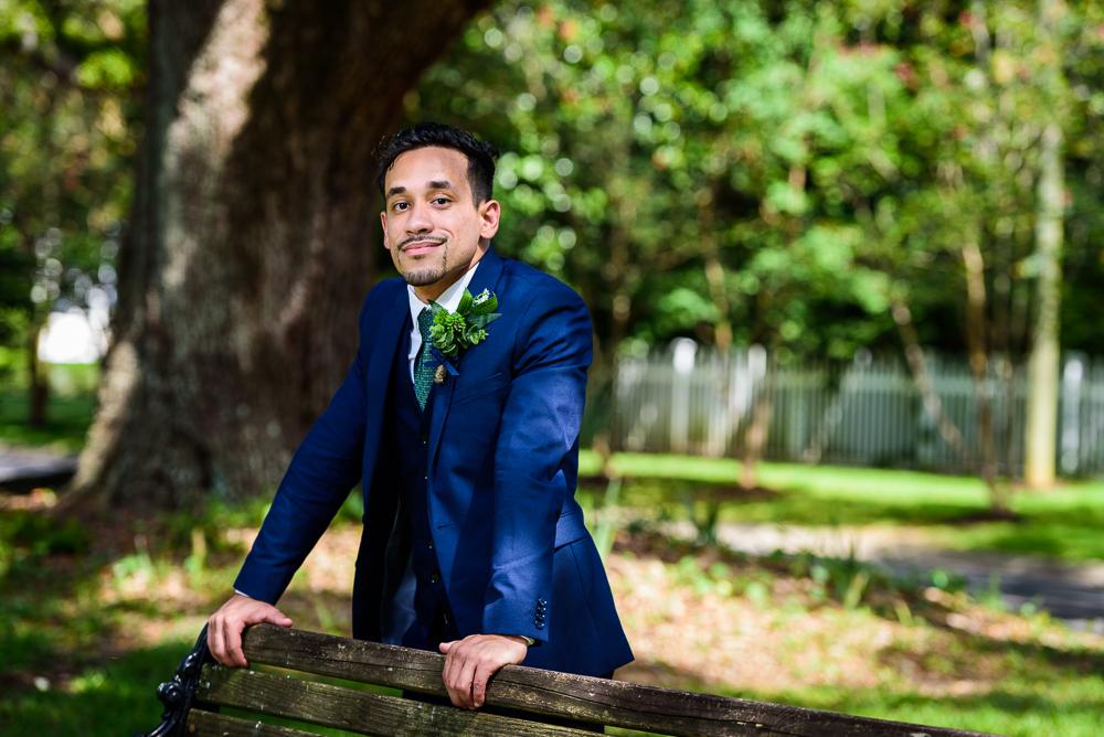 Groom leaning on a bench, blue and green wedding, The Garden Center, Pensacola Garden Wedding, Lazzat Photography, Florida wedding photographer photography