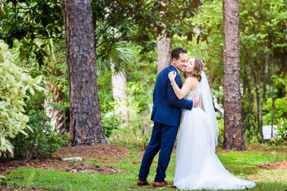 Bride kissing Groom on the cheek in the garden, The Garden Center, Pensacola Garden Wedding, Lazzat Photography, Florida wedding photographer photography