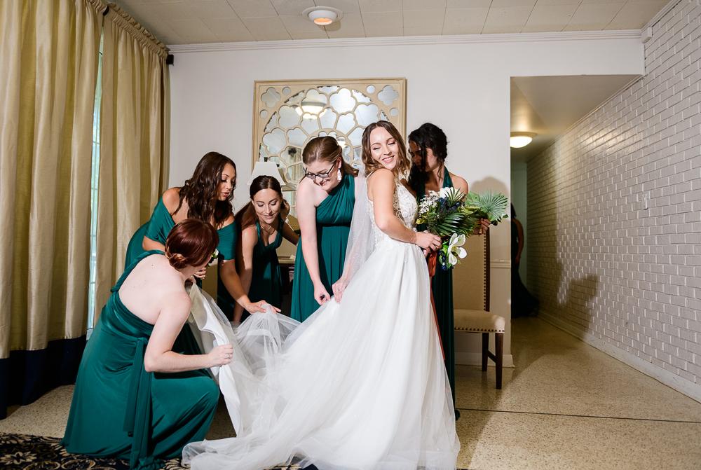 Bridesmaids doing Bride's bustle, The Garden Center, Pensacola Garden Wedding, Lazzat Photography, Florida wedding photographer photography