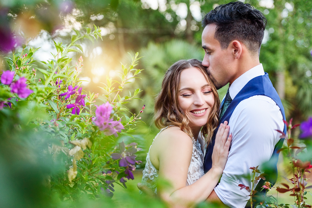 Groom kissing Bride's head in the garden, The Garden Center, Pensacola Garden Wedding, Lazzat Photography, Florida wedding photographer photography