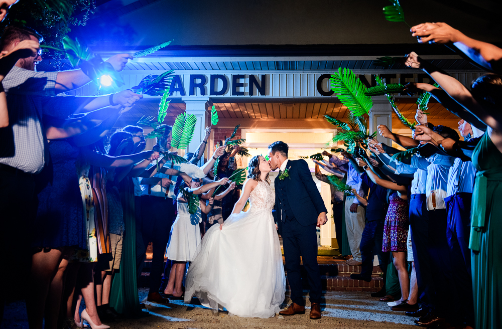 Bride and Groom kissing during grand exit with palm leaves, The Garden Center, Pensacola Garden Wedding, Lazzat Photography, Florida wedding photographer photography