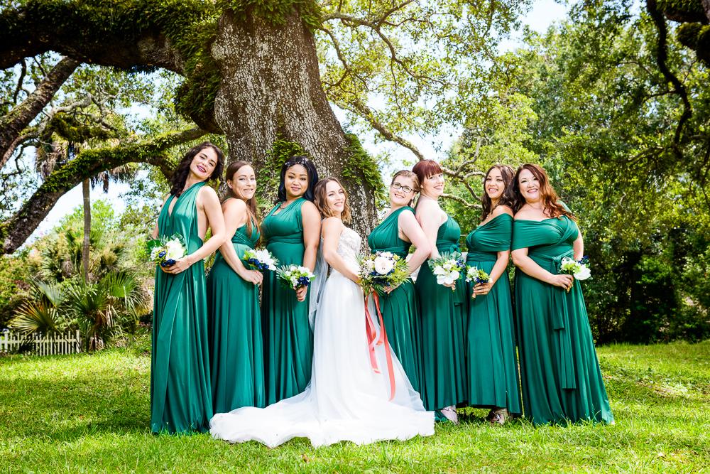Bride and Bridesmaids leaning on each other, green bridesmaid dress, blue and green wedding, The Garden Center, Pensacola Garden Wedding, Lazzat Photography, Florida wedding photographer photography
