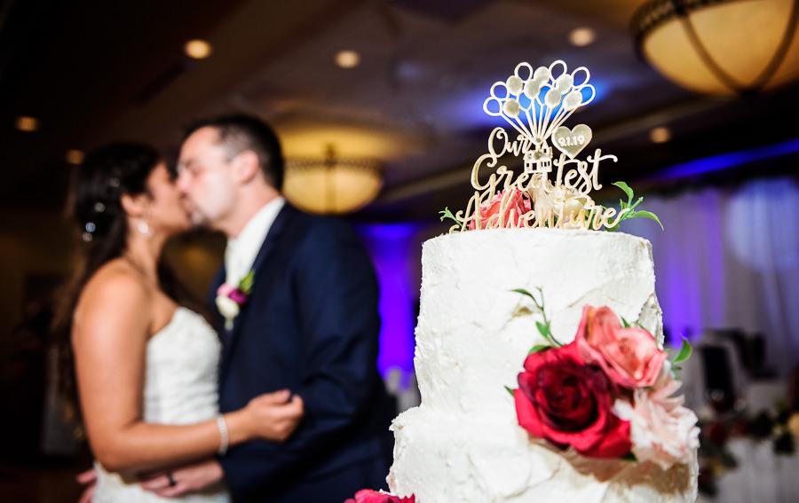 Bride and Groom kissing by their wedding cake, Hilton Garden Inn Pensacola Airport, Pensacola Summer Wedding, Lazzat Photography