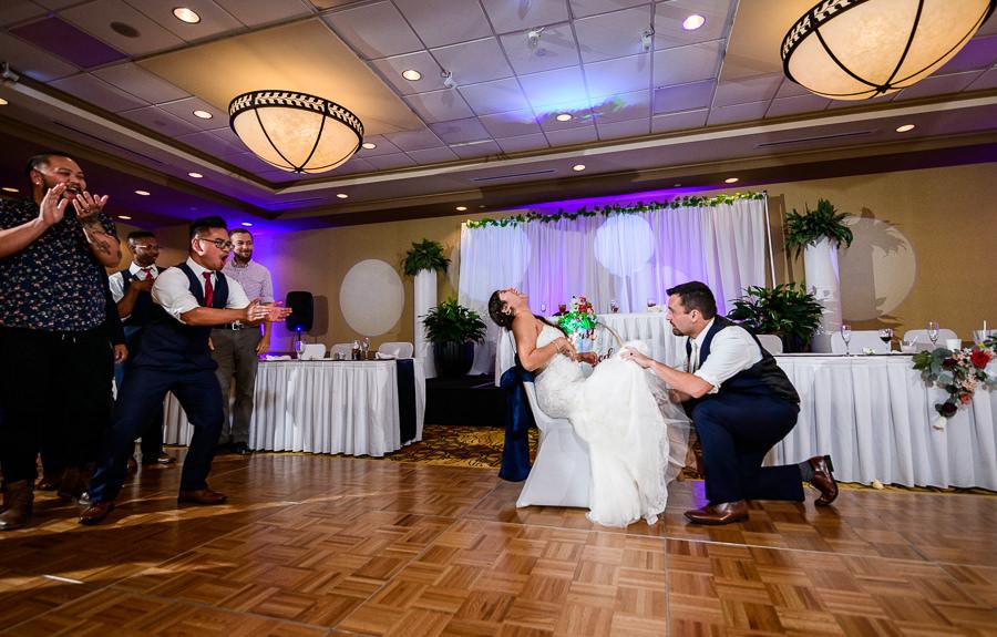 Groom getting the Bride's garter, Hilton Garden Inn Pensacola Airport, Pensacola Summer Wedding, Lazzat Photography