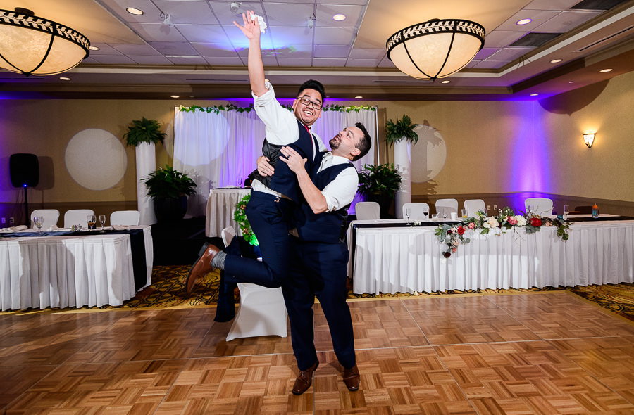 Groom lifting up Groomsmen who caught the garter, Hilton Garden Inn Pensacola Airport, Pensacola Summer Wedding, Lazzat Photography