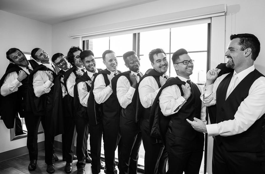 Groom looking at his groomsmen, Holiday Inn Express Pensacola Downtown, Pensacola Summer Wedding, Lazzat Photography