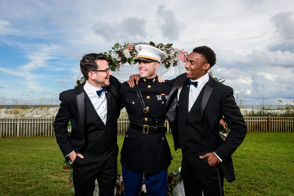 Groom and Groomsmen shoulder hug in front of wedding arch, Pensacola Beach Military Wedding, Hilton Pensacola Beach, Lazzat Photography, Florida Wedding Photography