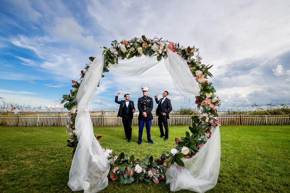 Groom and Groomsmen cheering behind wedding arch, Pensacola Beach Military Wedding, Hilton Pensacola Beach, Lazzat Photography, Florida Wedding Photography