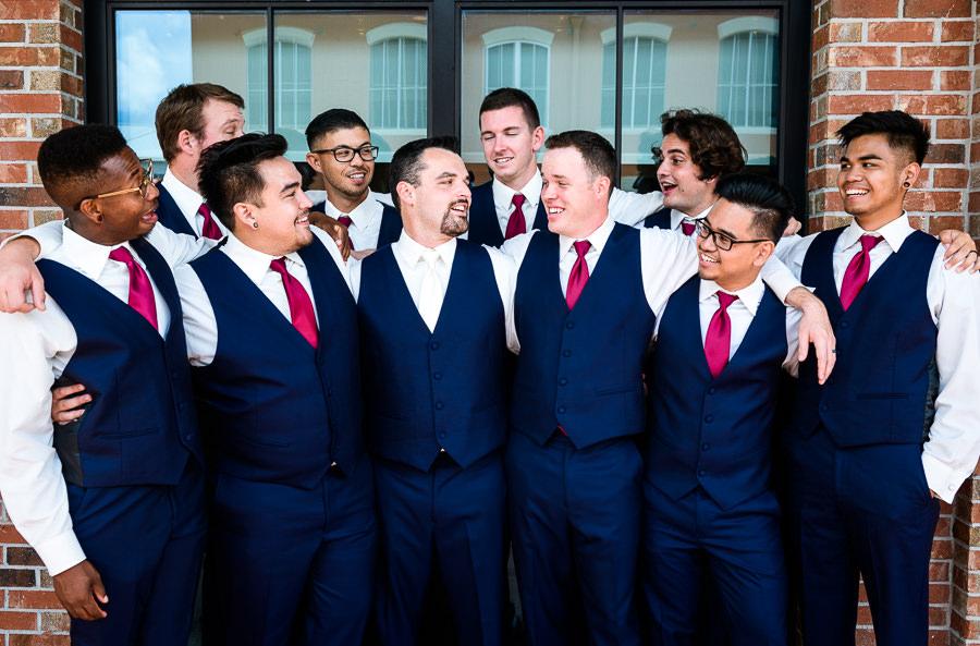 Groom shoulder hugging groomsmen, Blue and pink wedding, Holiday Inn Express Pensacola Downtown, Pensacola Summer Wedding, Lazzat Photography