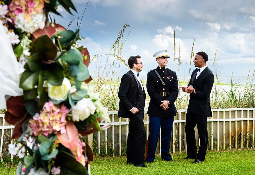 Groom talking with Groomsmen behind wedding arch, Pensacola Beach Military Wedding, Hilton Pensacola Beach, Lazzat Photography, Florida Wedding Photography