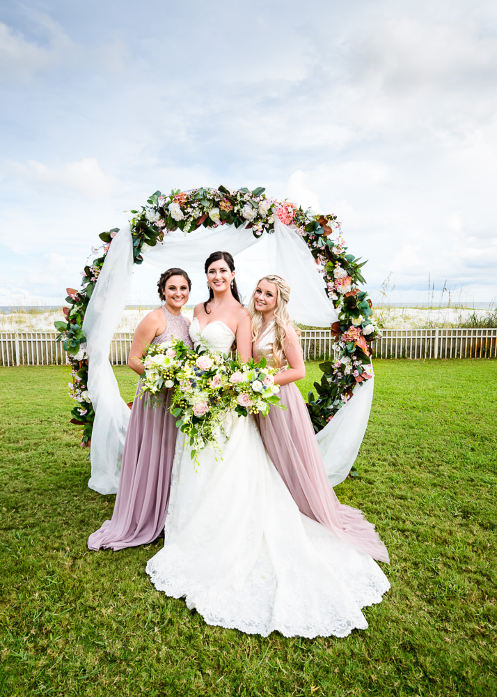 Bride with Bridesmaids in front of wedding arch, Pensacola Beach Military Wedding, Hilton Pensacola Beach, Lazzat Photography, Florida Wedding Photography