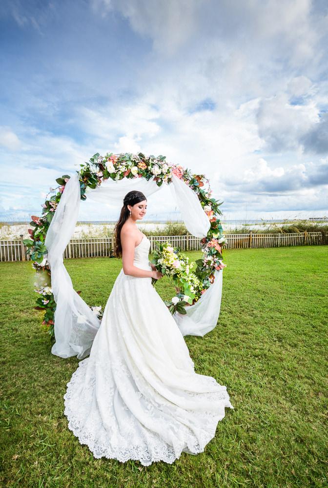 Bride in front of wedding arch, Pensacola Beach Military Wedding, Hilton Pensacola Beach, Lazzat Photography, Florida Wedding Photography