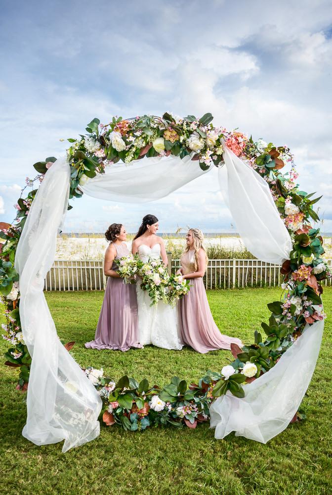 Bride and Bridesmaids behind wedding arch, Pensacola Beach Military Wedding, Hilton Pensacola Beach, Lazzat Photography, Florida Wedding Photography