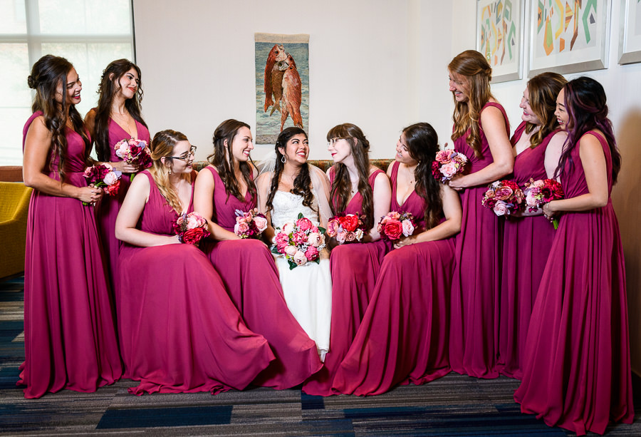 Bride and Bridesmaids smiling at each other, Magenta bridesmaid dresses, Holiday Inn Express Pensacola Downtown, Pensacola Summer Wedding, Lazzat Photography