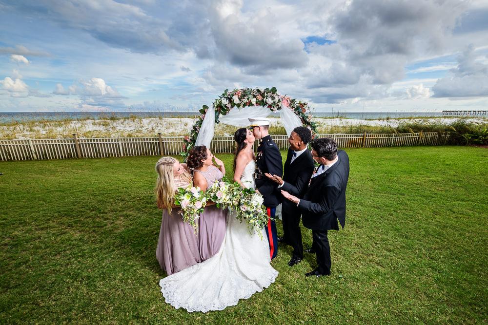 Wedding party cheer as Bride and Groom kiss under wedding arch, Pensacola Beach Military Wedding, Hilton Pensacola Beach, Lazzat Photography, Florida Wedding Photography