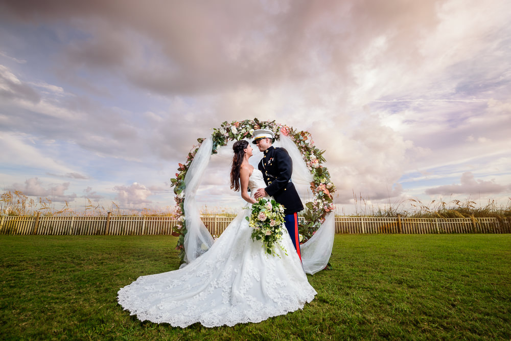 Bride and Groom smiling at each other under flower wedding arch, Pensacola Beach Military Wedding, Hilton Pensacola Beach, Lazzat Photography, Florida Wedding Photography