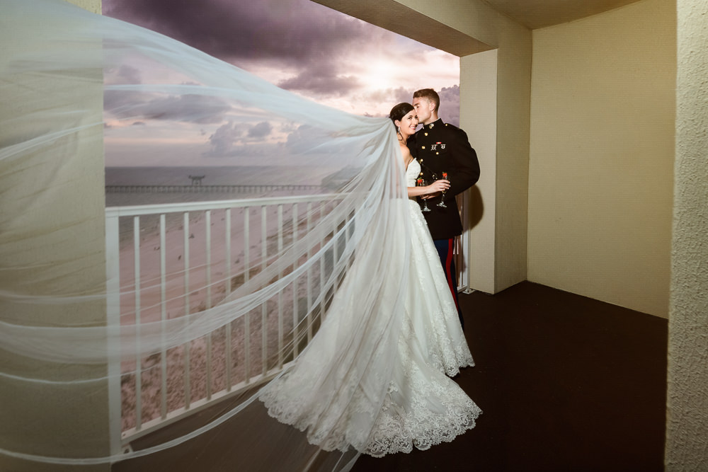 Bride and Groom on the balcony with veil flying, Pensacola Beach Military Wedding, Hilton Pensacola Beach, Lazzat Photography, Florida Wedding Photography