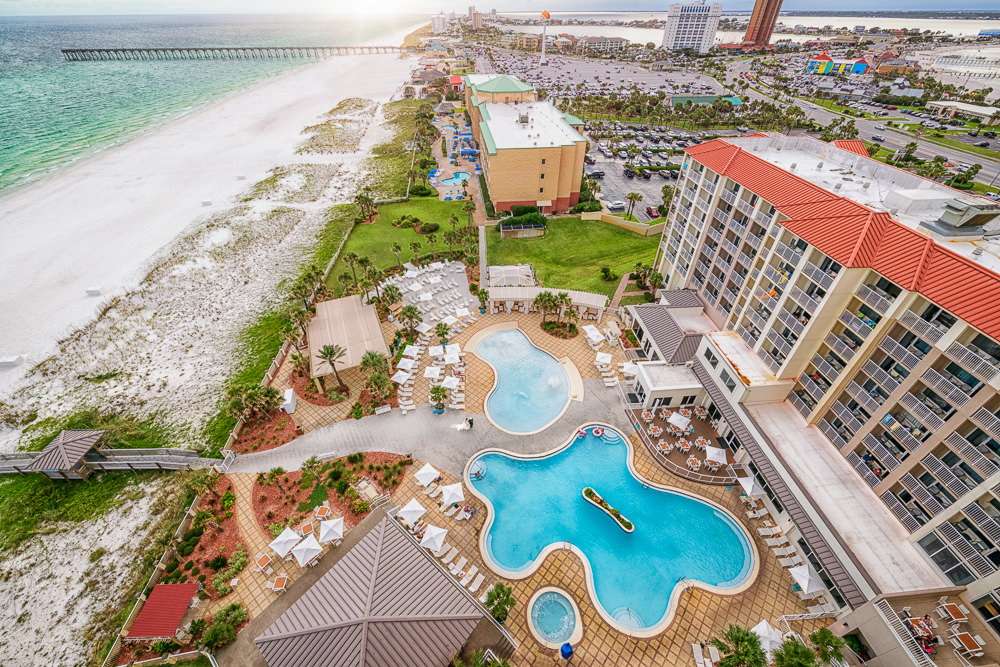 Bride and Groom walking between the pools from above with beach, Pensacola Beach Military Wedding, Hilton Pensacola Beach, Lazzat Photography, Florida Wedding Photography