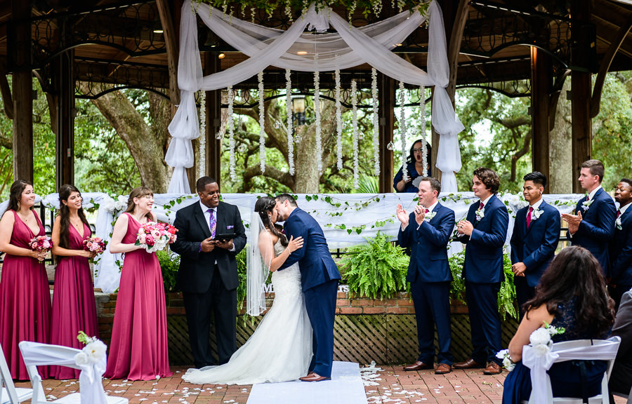 Bride and Groom's first kiss, blue and pink wedding, magenta bridesmaids dresses, seville square, Pensacola Summer Wedding, Lazzat Photography