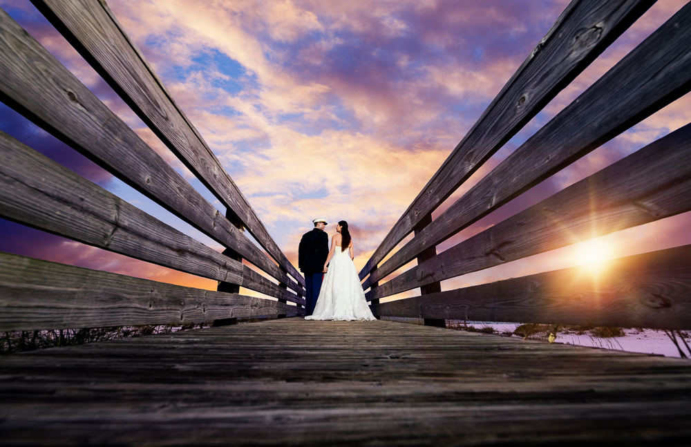 Bride and Groom looking at each other on the pier at sunset, Pensacola Beach Military Wedding, Hilton Pensacola Beach, Lazzat Photography, Florida Wedding Photography