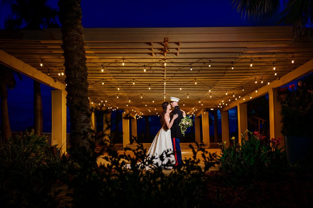 Bride and Groom at night under bistro lights, Pensacola Beach Military Wedding, Hilton Pensacola Beach, Lazzat Photography, Florida Wedding Photography