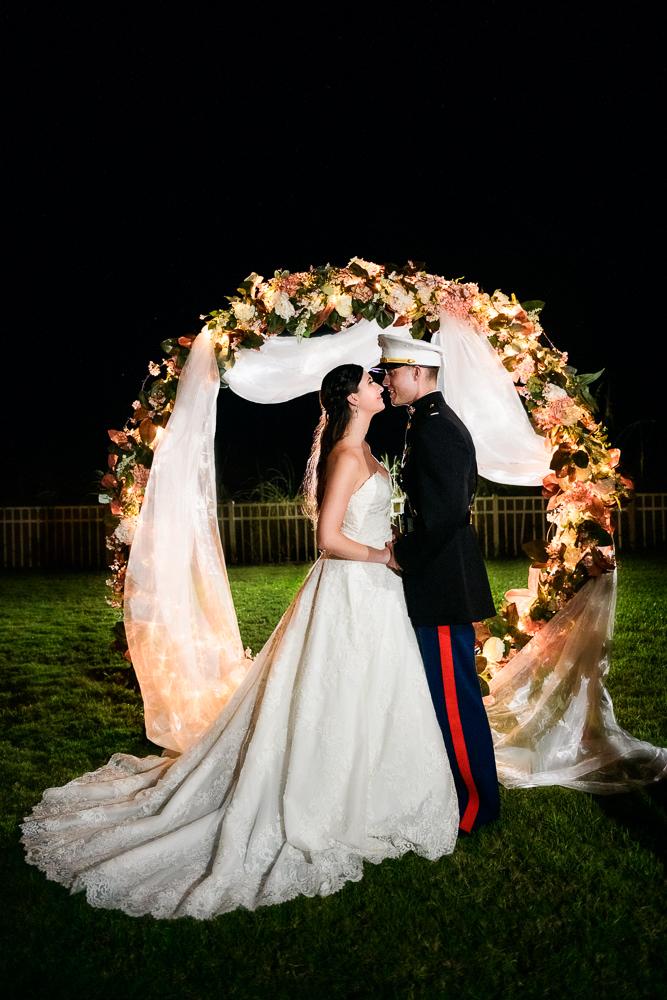 Bride and Groom smiling at each other under wedding arch, Pensacola Beach Military Wedding, Hilton Pensacola Beach, Lazzat Photography, Florida Wedding Photography