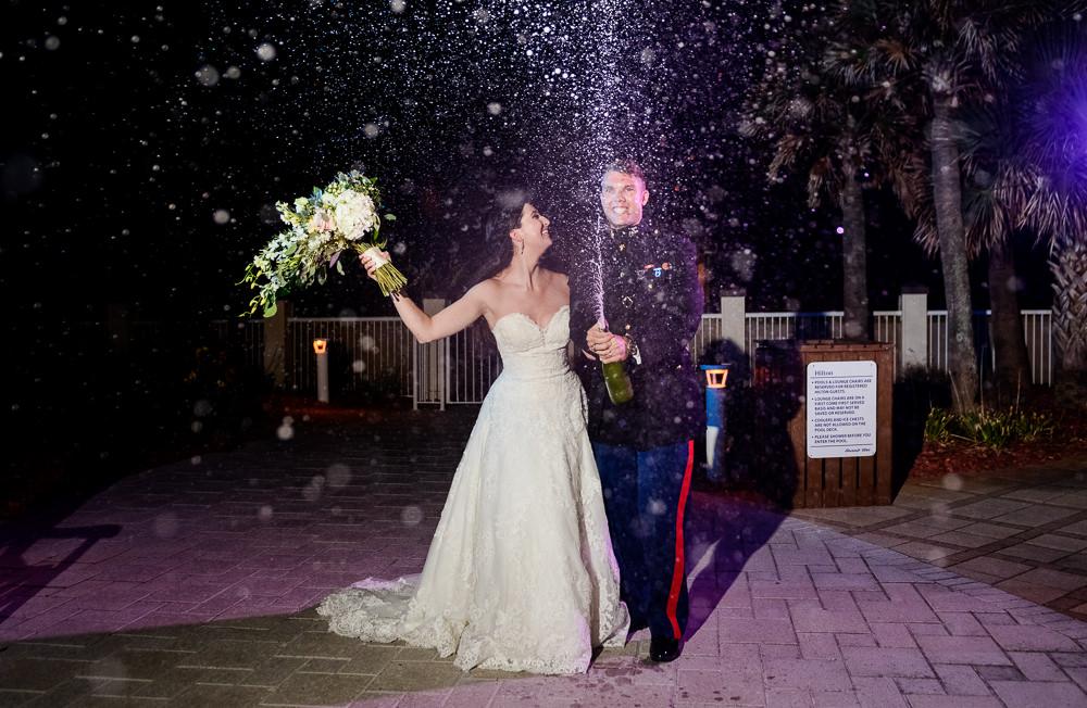 Bride and Groom spraying champagne, Pensacola Beach Military Wedding, Hilton Pensacola Beach, Lazzat Photography, Florida Wedding Photography