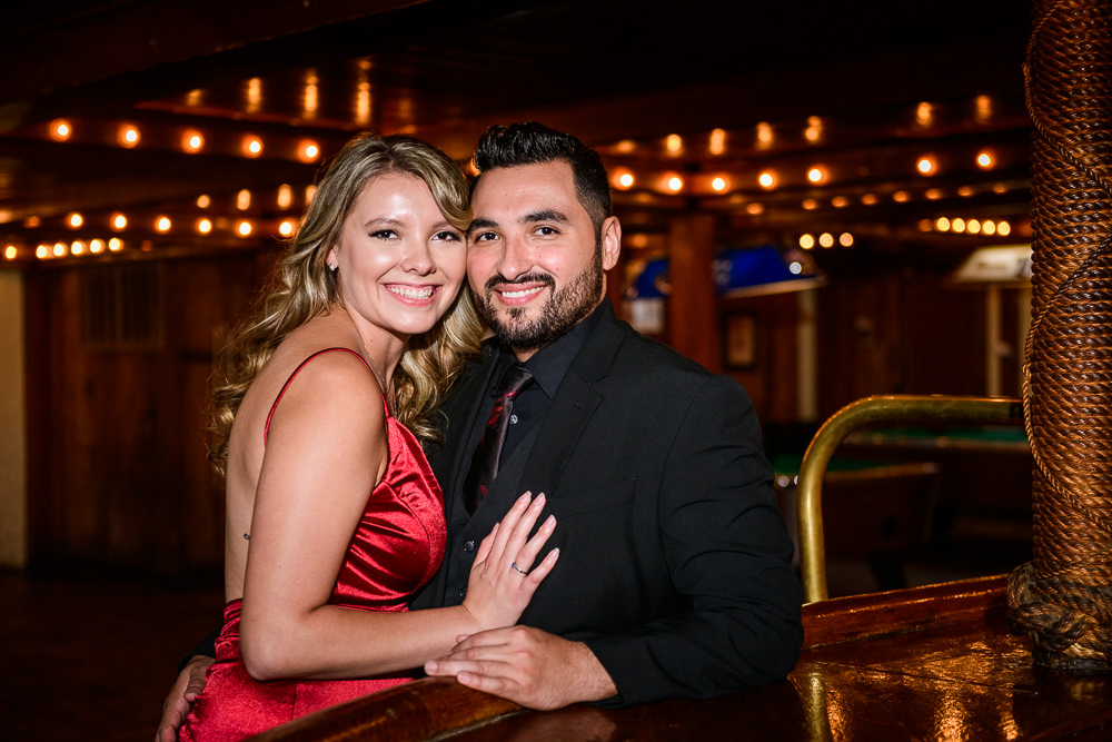 Couple smiling at the camera in Seville Quarter, New Orleans Inspired Engagement Session, Long red gown, Pensacola engagement photographer, Lazzat Photography