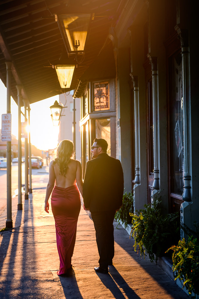 Couple walking down the street outside Seville Quarter, New Orleans Inspired Engagement Session, Long red gown, Pensacola engagement photographer, Lazzat Photography