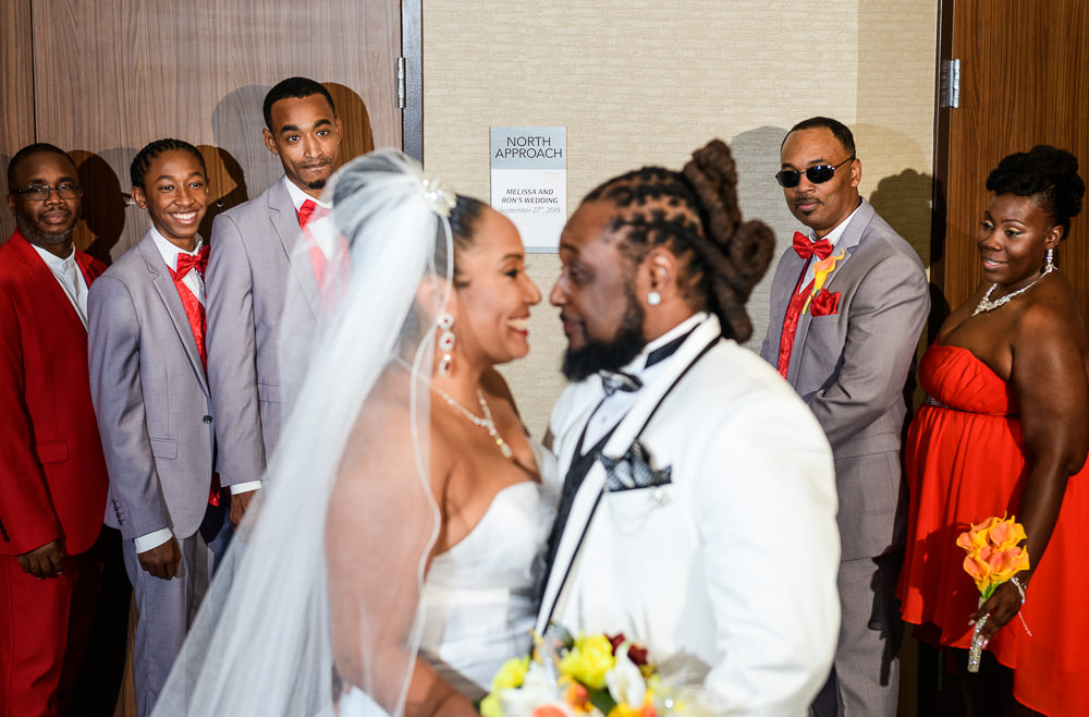 Bride and Groom smiling at each other during first look in front of their wedding party, Royal Red Destination Wedding, Florida wedding photographer, Lazzat Photography