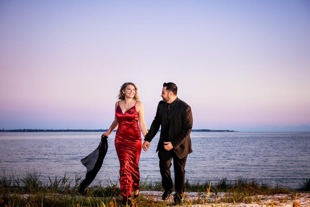 Couple walking together on the beach, New Orleans Inspired Engagement Session, Long red gown, Pensacola engagement photographer, Lazzat Photography