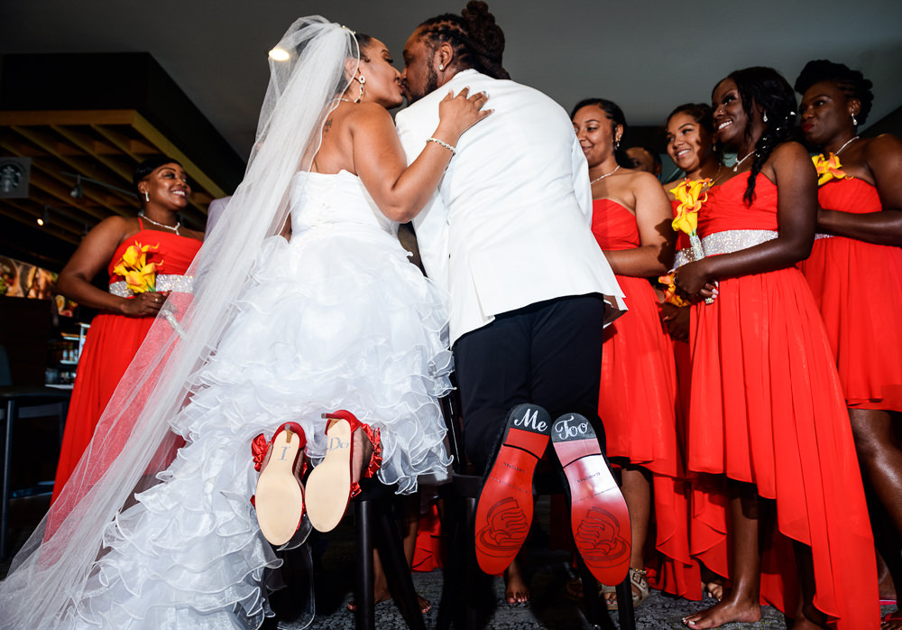 """Bride and Groom kissing while showing their shoe decals that say """"I Do"""" and """"Me Too"""", Royal Red Destination Wedding, Florida wedding photographer, Lazzat Photography"""