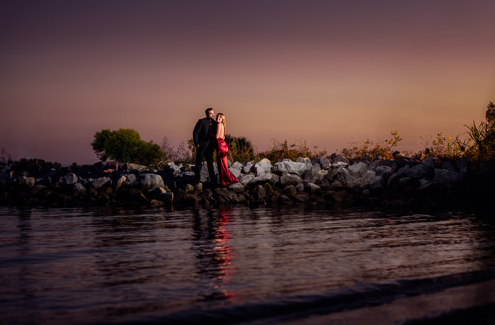 Couple standing on the rocks across the water at sunset, New Orleans Inspired Engagement Session, Long red gown, Pensacola engagement photographer, Lazzat Photography