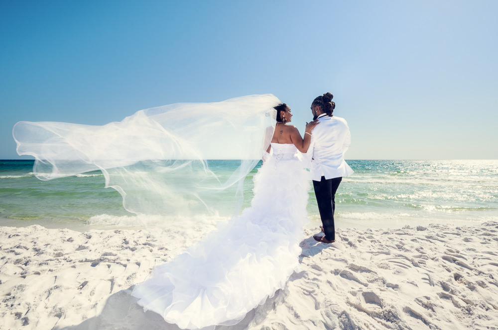 Bride and Groom on the beach facing the water with veil flying, Royal Red Destination Wedding, Florida wedding photographer, Lazzat Photography