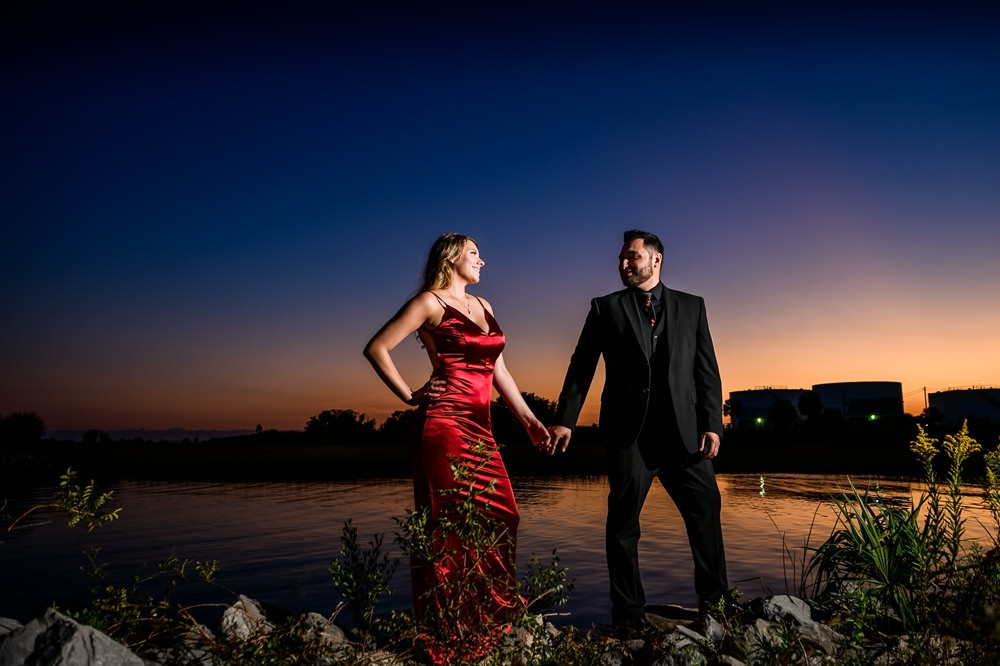 Couple look at each other holding hands on the water at sunset, New Orleans Inspired Engagement Session, Long red gown, Pensacola engagement photographer, Lazzat Photography