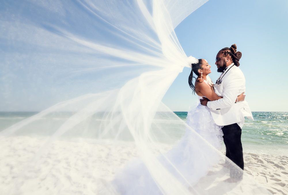 Bride and Groom hugging on the beach with veil flying towards camera, Royal Red Destination Wedding, Florida wedding photographer, Lazzat Photography