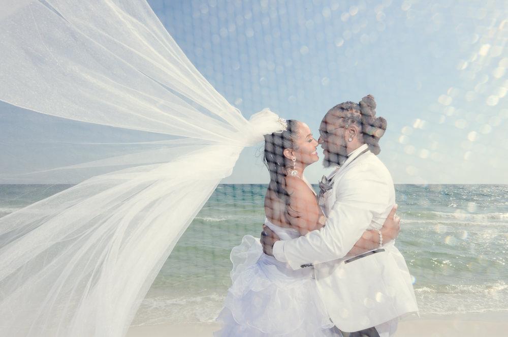 Bride and Groom hugging on the beach through the veil, Royal Red Destination Wedding, Florida wedding photographer, Lazzat Photography